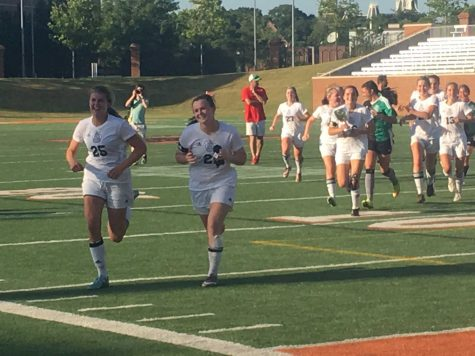 Seniors Caroline Laux, who scored a hat trick, and Abby Ott lead the team towards the student section.