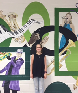 Another talent show participant, freshman Ann-Charlotte Langet, smiles broadly by the mural outside the auditorium.