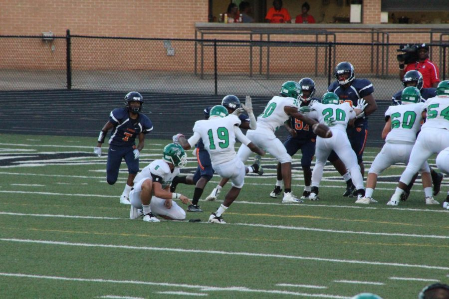 Senior kicker Baba Agbaje kicking an extra point following the touchdown by Cate
