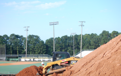 Bulldozer takes dirt from mound and moves it to the concrete foundation.