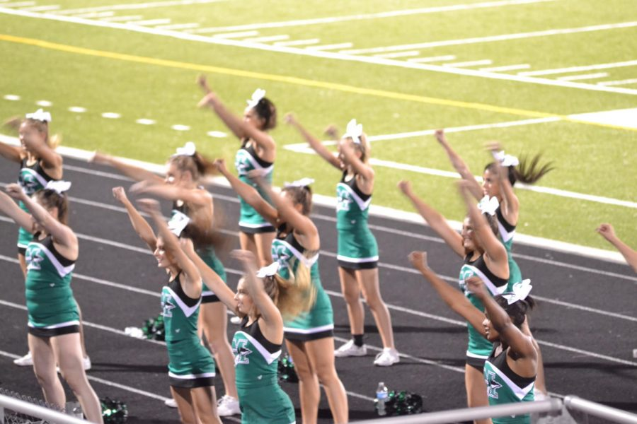 The football cheerleaders pump up the student section.