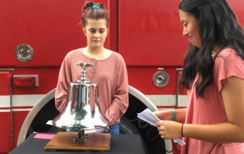 Sophomores Nadia Post and Lila Slay stand by the bell. Nadia Post reads a name off of a card and rings the bell three times. Lila Slay stops the bell after the third ring to symbolize the death of a person.