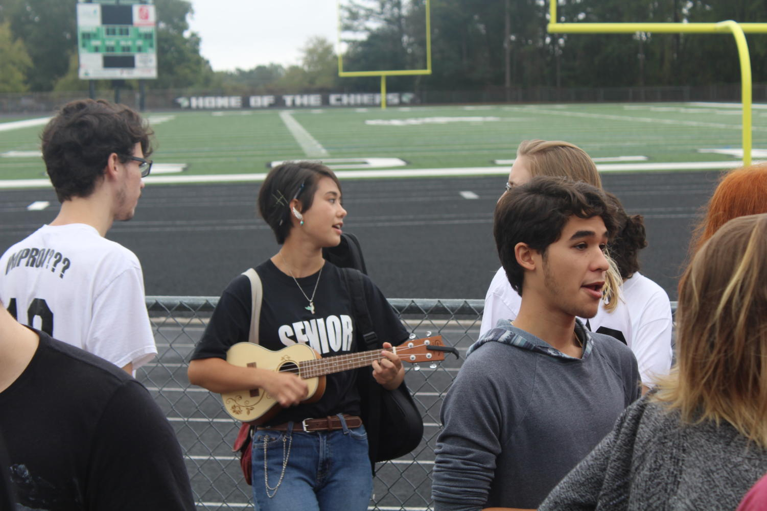 Senior Kylie Dickensen played her ukulele during the wait between picture taking