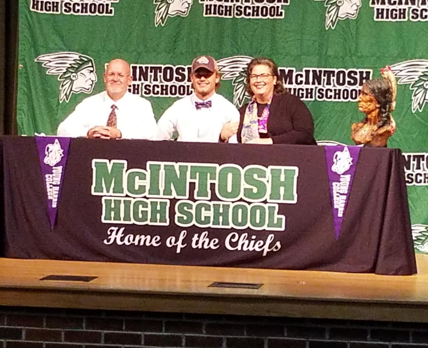 Senior Huck McCollum with his parents in the auditorium on signing day, on Thursday, November 15.