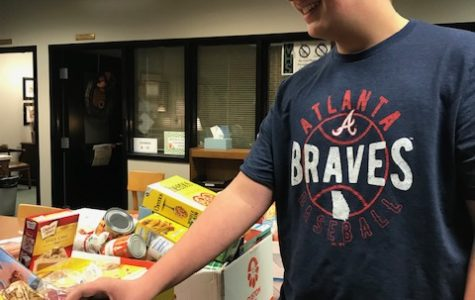 Ambassador and sophomore Grant Fouts donates food for the families in need.