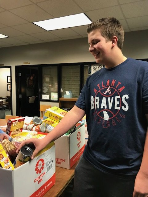 Ambassador+and+sophomore+Grant+Fouts+donates+food+for+the+families+in+need.