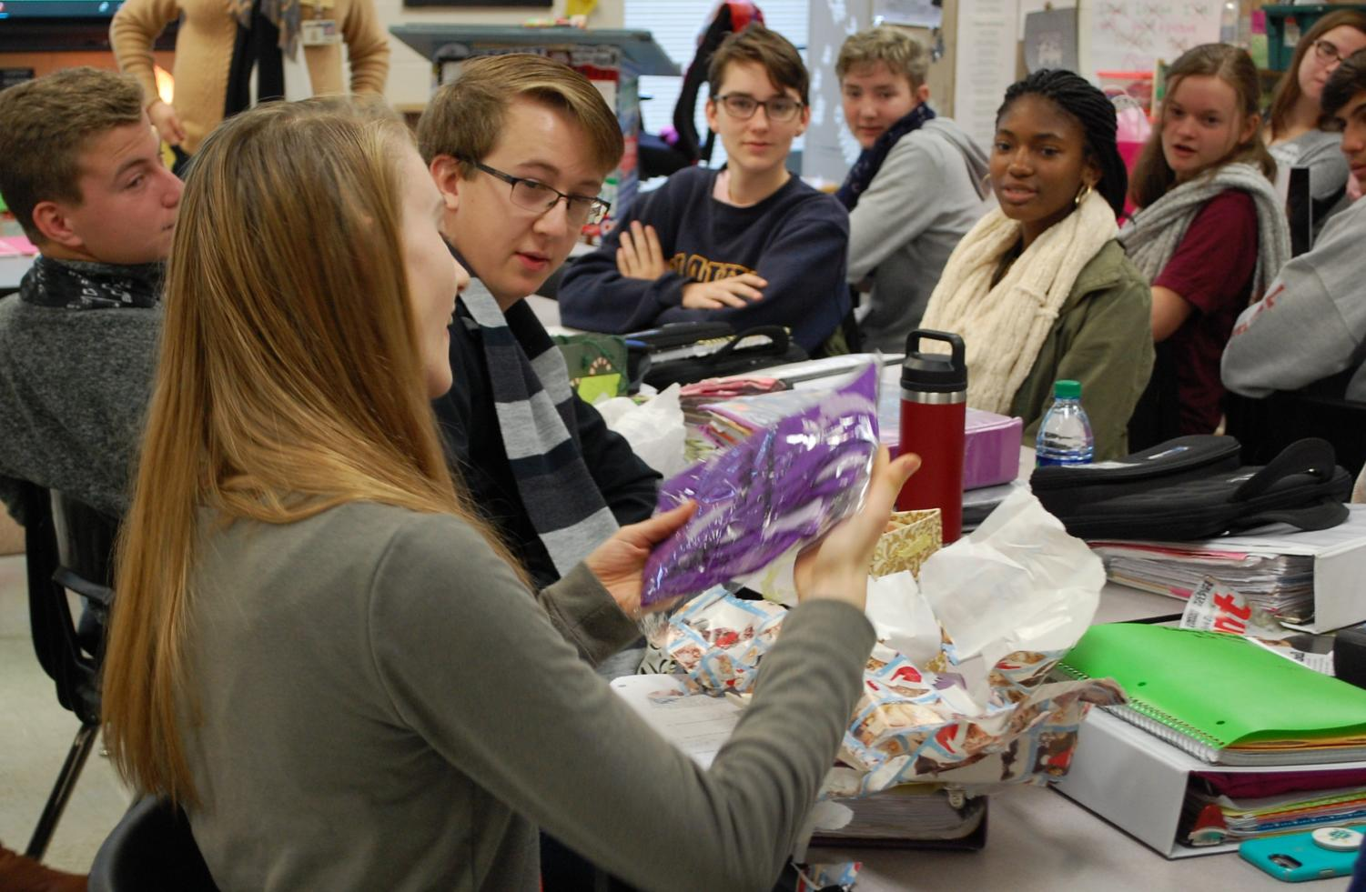 Students watch intently as classmate Rebecca Zack unwraps her scarf.
