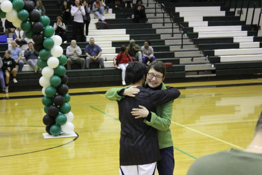 Senior+manager+Nelson+White+hugs+mother+after+being+recognized+for+four+years+of+assisting+the+basketball+program.