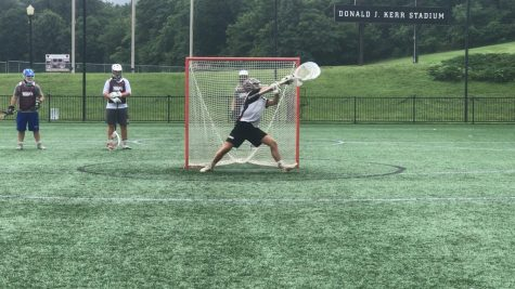 Senior goalie for the Chiefs, Huck McCollum, saving a shot during practice.
