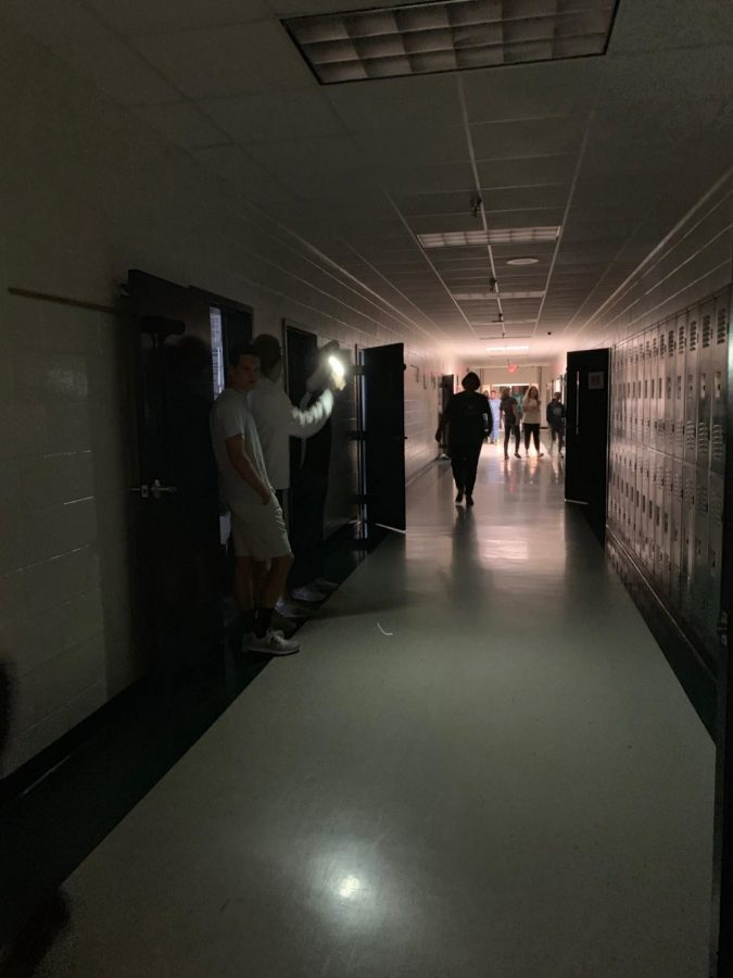 Brad+Yarbrough+using+his+phone+flashlight+to+lighten+up+some+of+the+hallway.+