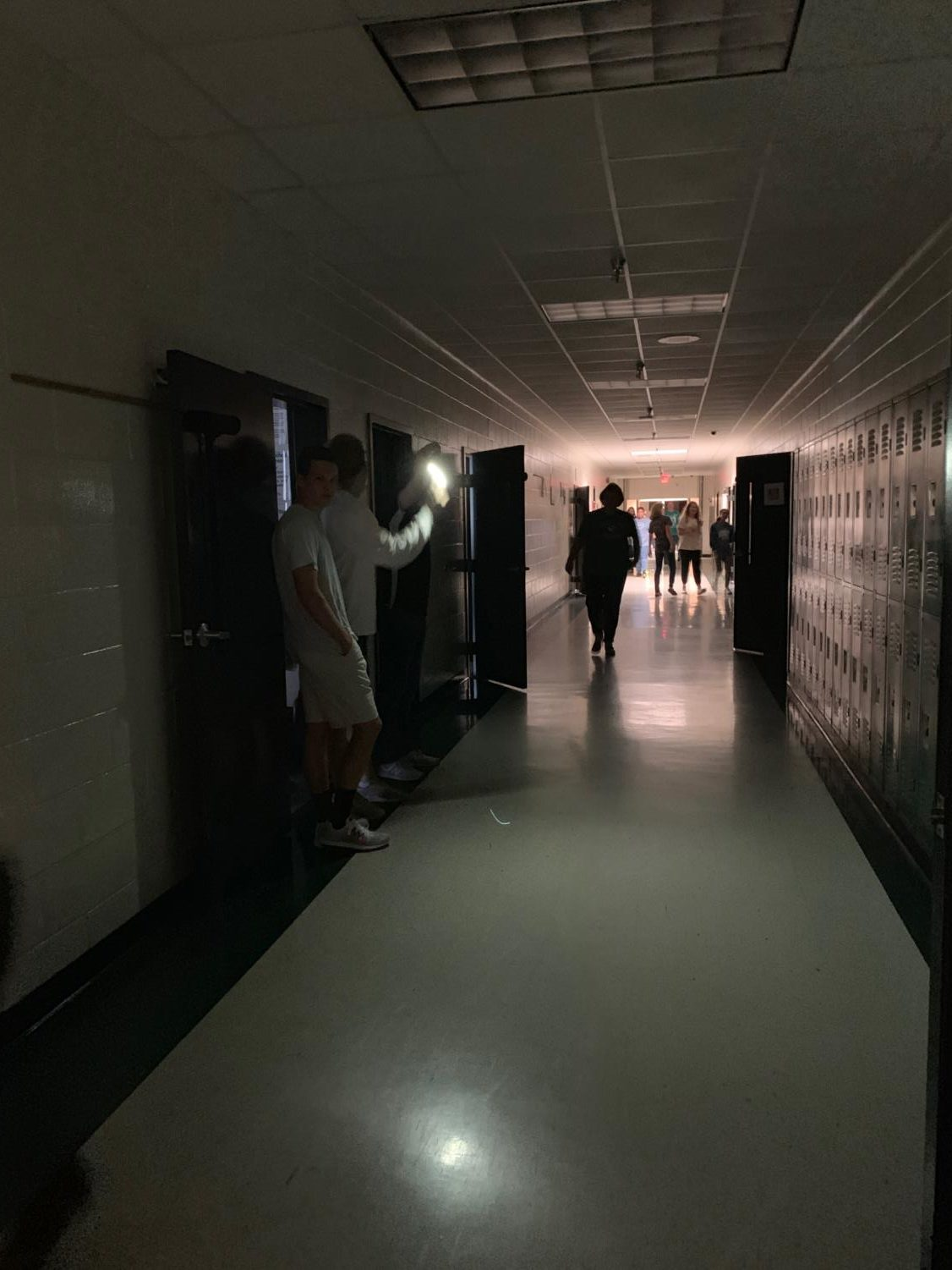 Brad Yarbrough using his phone flashlight to lighten up some of the hallway.
