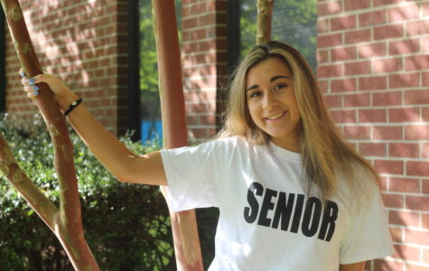 Senior Cailey Hardman poses in the courtyard while wearing her senior shirt.