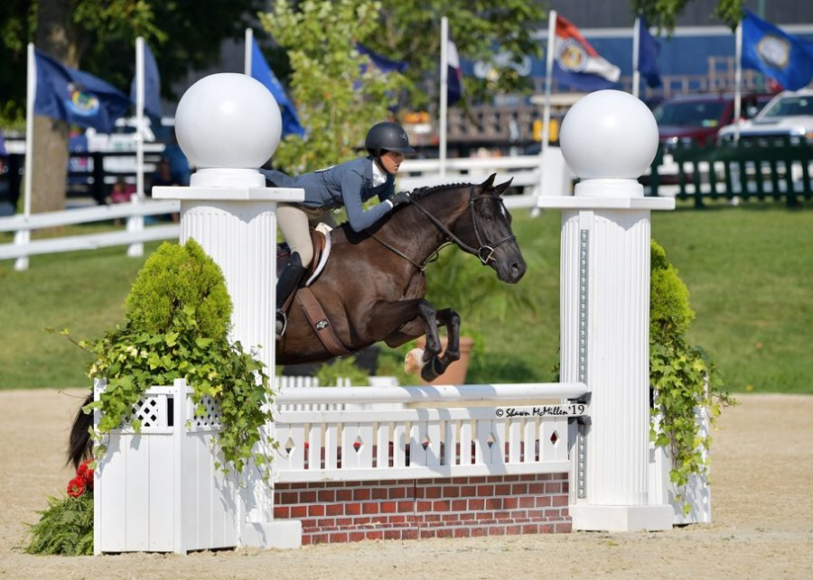 Abby Rauch mid jump at one of her horse shows.