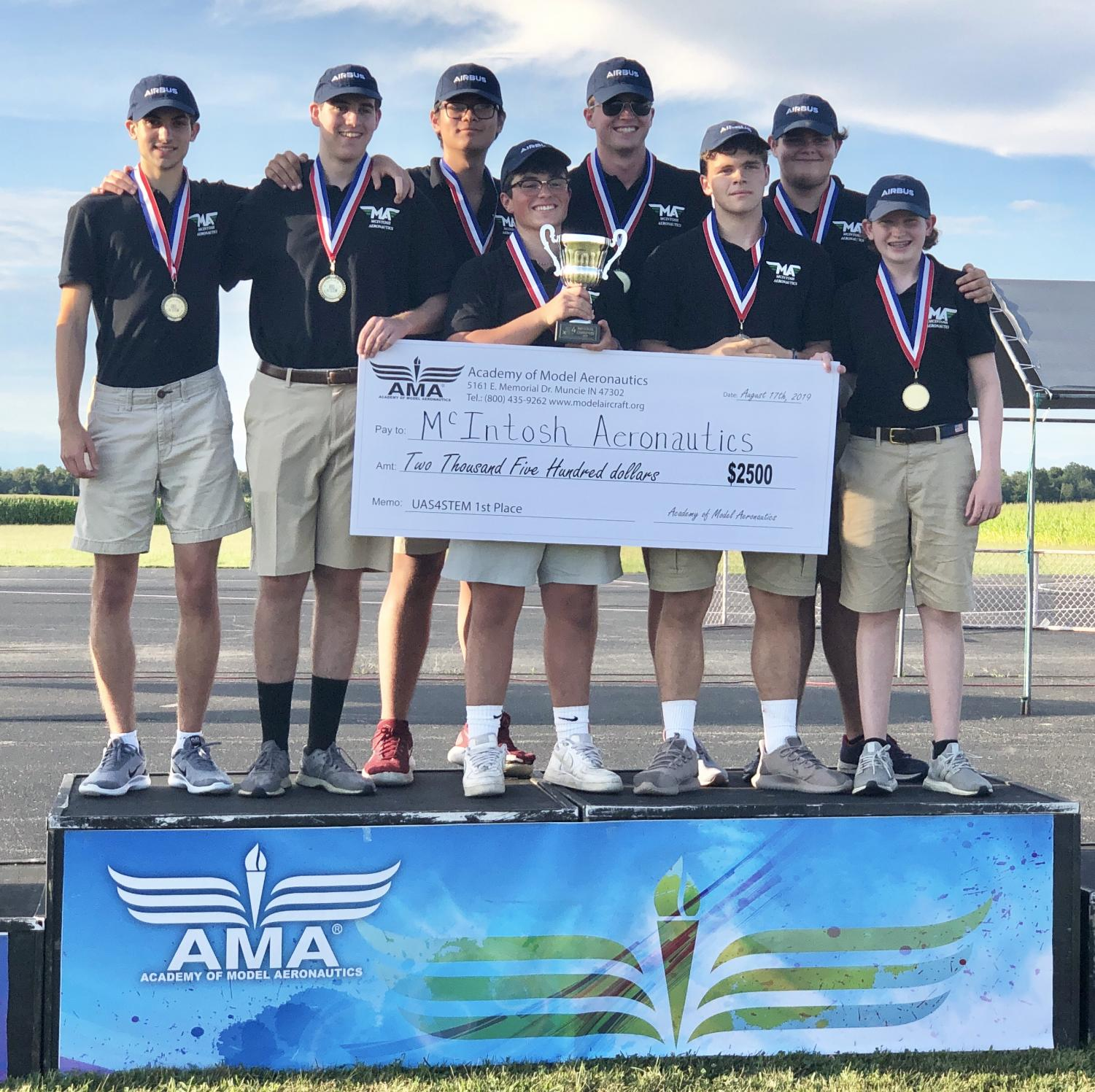 The McIntosh Aeronautics team poses atop the championship podium after receiving their trophy and prize check.