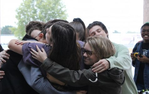 The cast of Bellwether gets together for a group hug before their big performance for the judges.