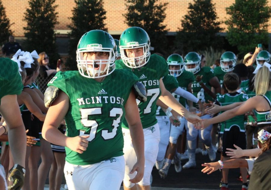 Jacob Dalton and Reitter Bowers exiting the locker room while future McIntosh students and athletes wish them luck with a high five before a game.