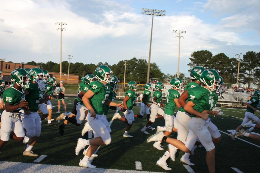 The MHS football team rushing onto the field.